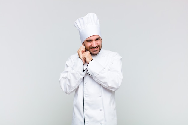 Kale man verliefd voelen en op zoek schattig, schattig en gelukkig, romantisch glimlachend met handen naast gezicht