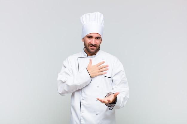 Kale man voelt zich gelukkig en verliefd, glimlachend met de ene hand naast het hart en de andere strekt zich vooraan uit