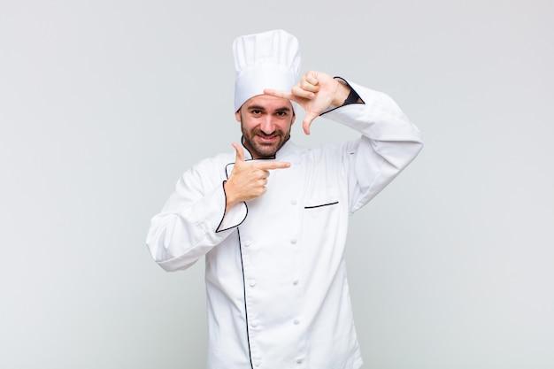 Kale man voelt zich gelukkig, vriendelijk en positief, lacht en maakt een portret of fotolijst met handen