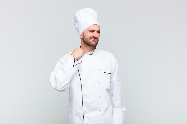 Kale man voelt zich gestrest, angstig, moe en gefrustreerd, trekt aan de hals van het shirt en kijkt gefrustreerd door het probleem