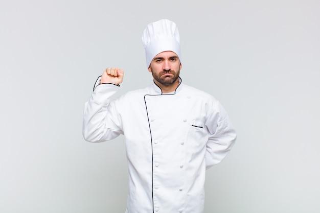 Kale man voelt zich serieus, sterk en rebels, steekt zijn vuist op, protesteert of vecht voor revolutie