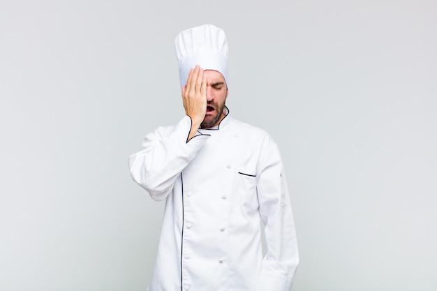 Kale man ziet er slaperig, verveeld en geeuwend uit, met hoofdpijn en één hand die de helft van het gezicht bedekt