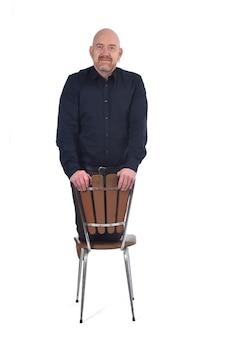 Kale man zit op zijn knieën in een stoel
