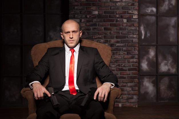 Kale moordenaar in pak en rode stropdas zittend in een stoel en pistolen in handen te houden