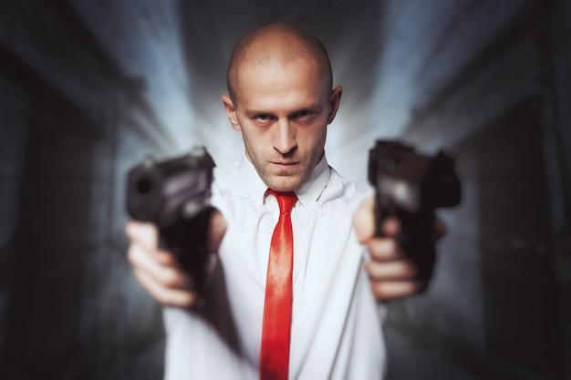 Kale moordenaar in rode stropdas mikt met twee pistolen.