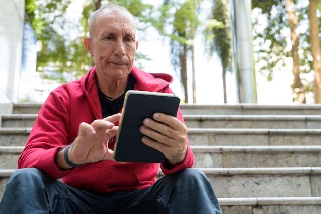 Kale senior man met behulp van digitale tablet zittend op de trap