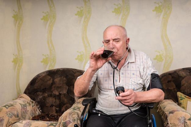 Kale senior man met speciale behoeften op zijn rolstoel in de woonkamer, een bloeddrukmeter lezend terwijl hij een glas gezond sap drinkt.