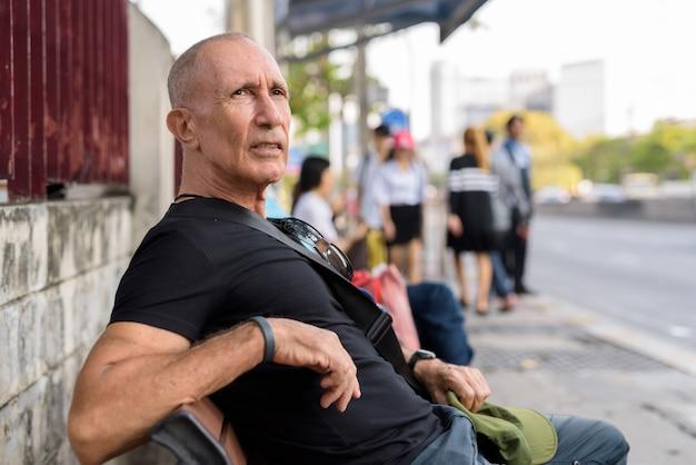 Kale senior toeristische man wachten en zittend op een houten bankje bij de bushalte