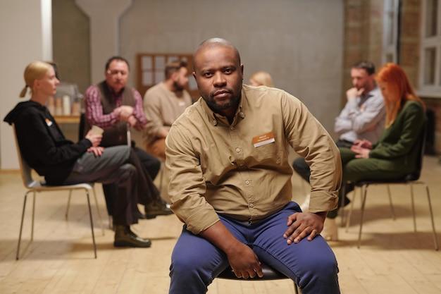 Kale serieuze man van afrikaanse etniciteit in vrijetijdskleding die naar je kijkt terwijl hij op een stoel zit tegen verschillende patiënten van de mentale steungroep