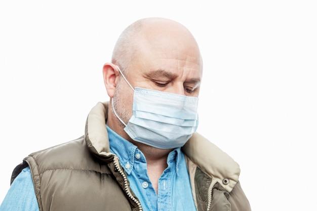 Kale volwassen man in een medisch masker op een witte muur. detailopname. voorzorgsmaatregelen in quarantaine geplaatst voor de periode van de coronviruspandemie. ruimte voor tekst.