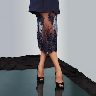 Kale vrouwelijke benen in hoge hakschoenen.
