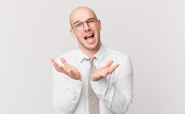 Kale zakenman die er wanhopig en gefrustreerd uitziet, gestrest, ongelukkig en geïrriteerd, schreeuwend en schreeuwend?