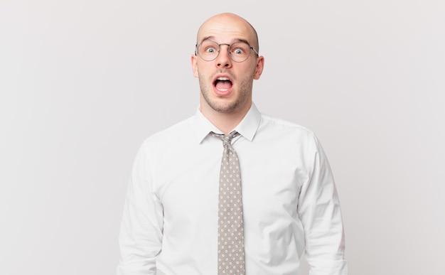 Kale zakenman die erg geschokt of verrast kijkt, starend met open mond en zegt wow