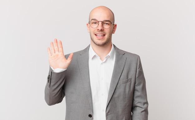 Kale zakenman die gelukkig en opgewekt glimlacht, met de hand zwaait, je verwelkomt en begroet, of afscheid neemt