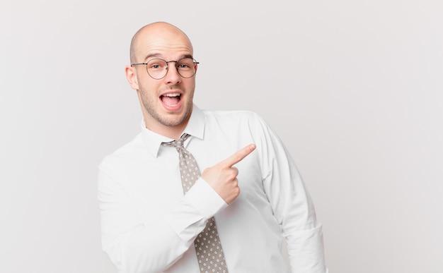 Kale zakenman die opgewonden en verrast kijkt en naar de zijkant en naar boven wijst om ruimte te kopiëren