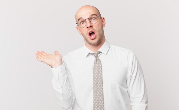 Kale zakenman die verrast en geschokt kijkt, met open mond terwijl hij een object vasthoudt met een open hand aan de zijkant