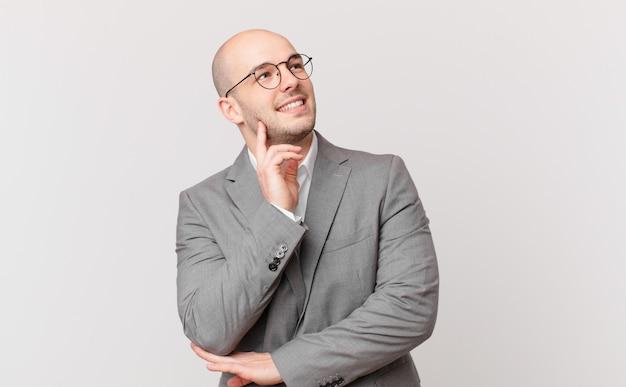 Kale zakenman die vrolijk lacht en dagdroomt of twijfelt, opzij kijkend