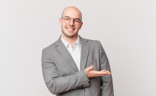 Kale zakenman die vrolijk lacht, zich gelukkig voelt en een concept in kopieerruimte toont met de palm van de hand