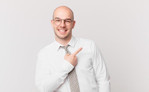 Kale zakenman die vrolijk lacht, zich gelukkig voelt en naar de zijkant en naar boven wijst, een object in de kopieerruimte laat zien