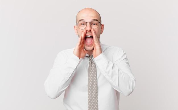Kale zakenman die zich gelukkig, opgewonden en positief voelt, een grote schreeuw geeft met de handen naast de mond, roept