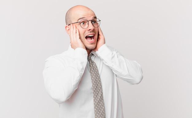 Kale zakenman die zich gelukkig, opgewonden en verrast voelt, opzij kijkend met beide handen op het gezicht