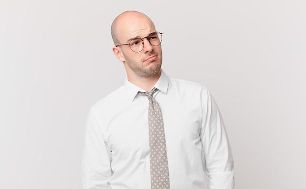 Kale zakenman die zich verdrietig, overstuur of boos voelt en opzij kijkt met een negatieve houding, fronsend in onenigheid