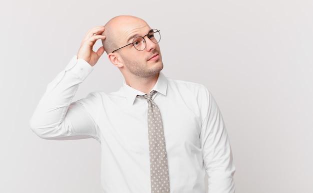 Kale zakenman die zich verward en verward voelt, hoofd krabt en opzij kijkt