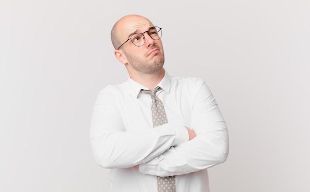 Kale zakenman die zijn schouders ophaalt, zich verward en onzeker voelt, twijfelt met gekruiste armen en een verbaasde blik