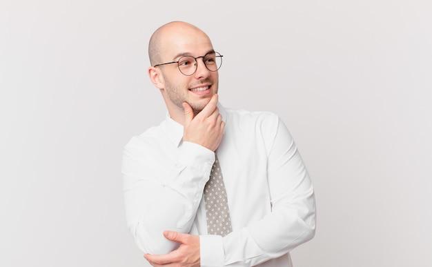 Kale zakenman glimlachend met een gelukkige, zelfverzekerde uitdrukking met de hand op de kin, zich afvragend en opzij kijkend
