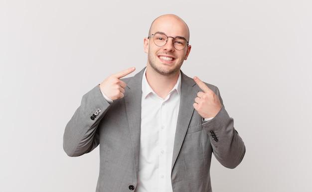 Kale zakenman glimlachend vol vertrouwen wijzend naar eigen brede glimlach, positieve, ontspannen, tevreden houding