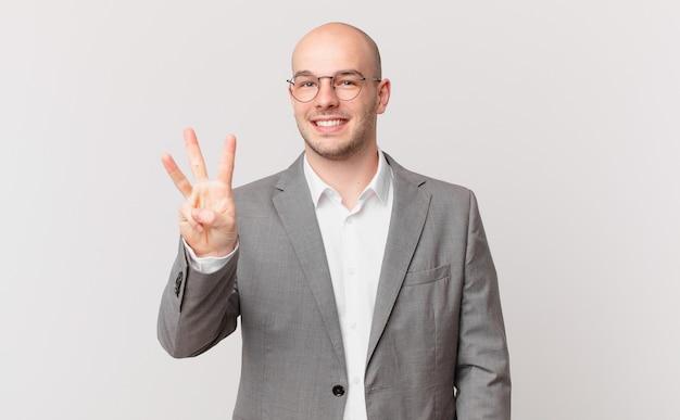 Kale zakenman glimlacht en ziet er vriendelijk uit, toont nummer drie of derde met hand naar voren, aftellend