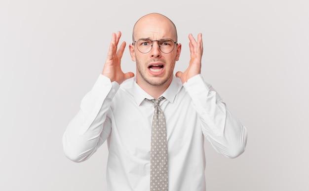 Kale zakenman schreeuwend met handen in de lucht, woedend, gefrustreerd, gestrest en overstuur?
