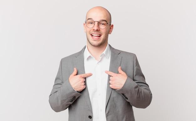 Kale zakenman voelt zich gelukkig, verrast en trots, wijzend naar zichzelf met een opgewonden, verbaasde blik