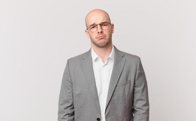 Kale zakenman voelt zich verdrietig en zeurderig met een ongelukkige blik, huilend met een negatieve en gefrustreerde houding