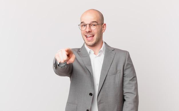 Kale zakenman wijzend op camera met een tevreden, zelfverzekerde, vriendelijke glimlach, jou kiezen