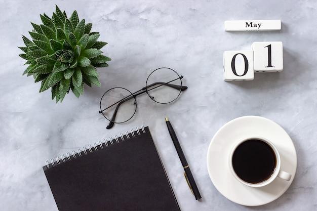 Kalender 1 mei. zwarte kladblok, kopje koffie, succulent, bril concept stijlvolle werkplek plat leggen