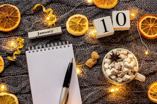 Kalender 10 januari beker van cacao en lege open notitieblok
