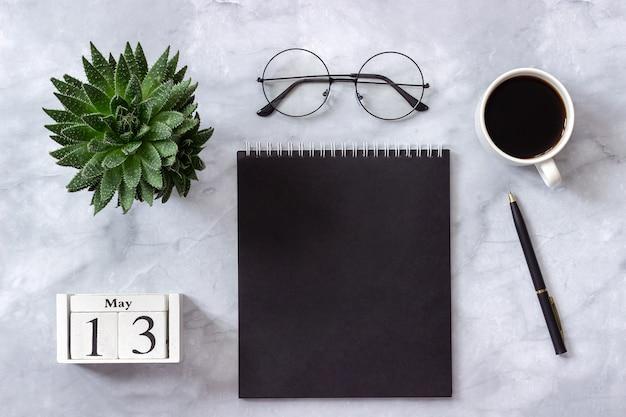 Kalender 13 mei. zwarte notitieblok, kopje koffie, succulent, glazen op marmer