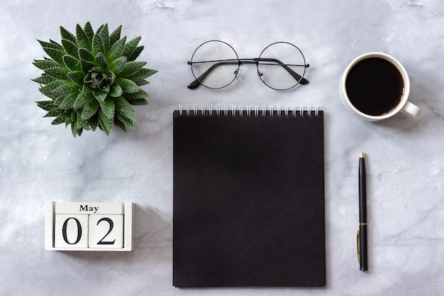 Kalender 2 mei. zwarte blocnote, kop koffie, succulent, glazen op marmer