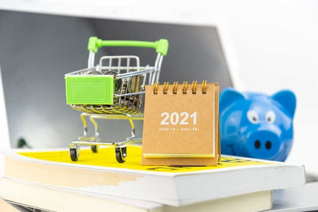 Kalender 2021 en mini-winkelwagentje met munt in de winkelwagen op boek met schermachtergrond. financieel, zaken, winkelen, kennisconcept.