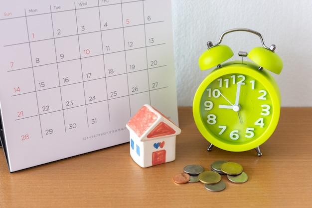 Kalender en huis op tafel. dag van het kopen of verkopen van een huis of betaling voor huur of lening.