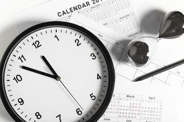 Kalender en klok op witte achtergrond