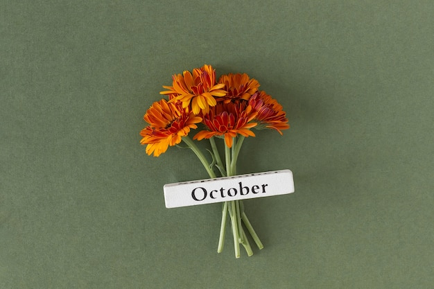 Kalender herfst maand oktober en oranje bloemen op groene achtergrond. bovenaanzicht plat lag. minimaal concept hallo herfst. sjabloon voor uw ontwerp, wenskaart
