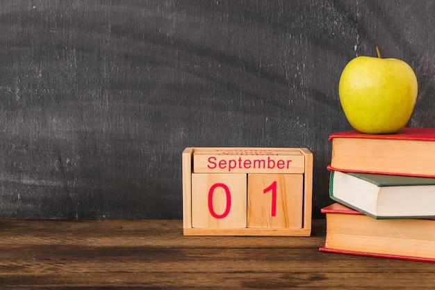 Kalender in de buurt van appel en boeken