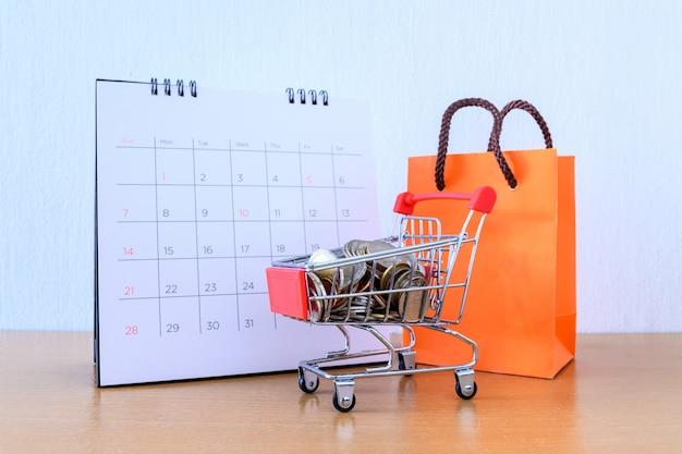 Kalender met dagen en kar supermarkt en oranje papieren zak op houten tafel. winkelen concept