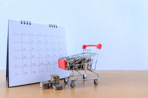 Kalender met dagen en kar supermarkt op houten tafel. winkelen concept