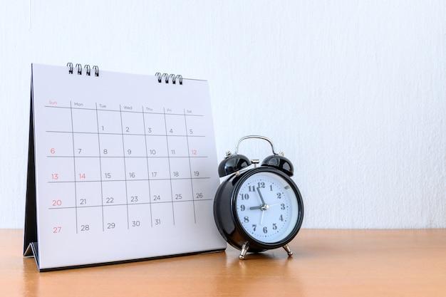 Kalender met dagen en klok op houten tafel