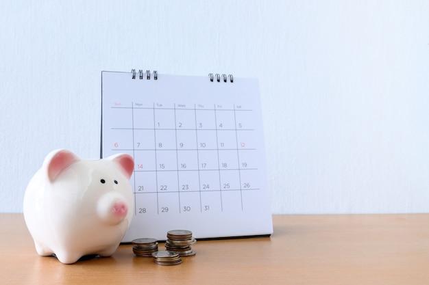 Kalender met dagen en spaarpot op houten tafel