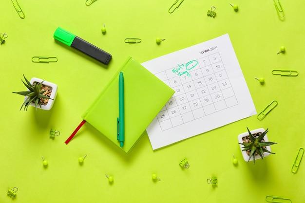Kalender met gemarkeerde datum van april fool's day en briefpapier op kleuroppervlak