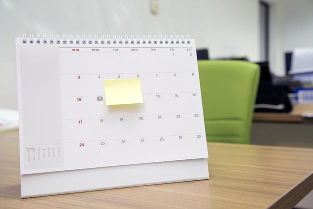 Kalender met papieren notitiebericht op bureau voor evenementenplanner is druk of bezig met plannen